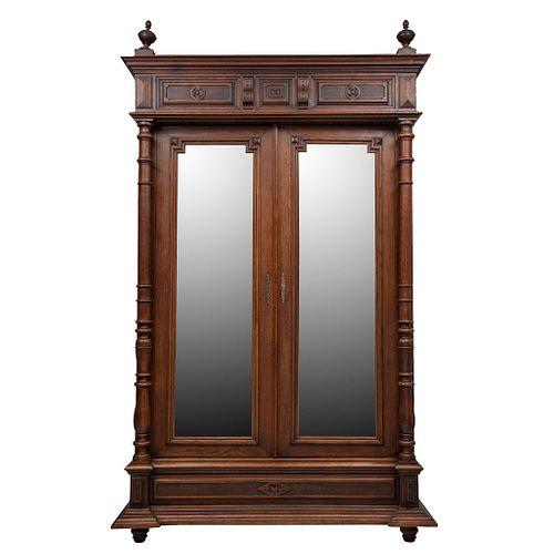 Armario.  Francia.  Siglo XX.  Estilo Enrique II.  En talla de madera de nogal.  Con 2 puertas abatibles, con espejo.