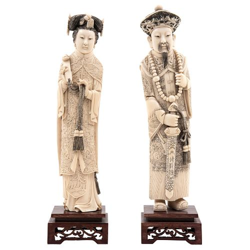 """IMPERIAL COUPLE CHINA, 20TH CENTURY Ivory carving with sgraffito and inked motifs; openwork wooden bases 11.8"""" (30 cm) tall"""