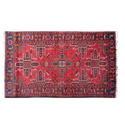 Tapete. Siglo XX. Anudado a mano en fibras de lana y algodón. Decorado con motivos florales y geométricos sobre fondo carmín.