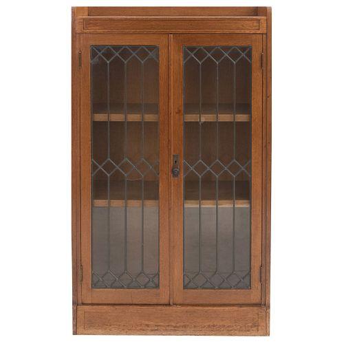 Librero. Siglo XX. Elaborado en madera. Con 2 puertas abatibles de vidrio, entrepaños internos, soportes tipo zócalo.