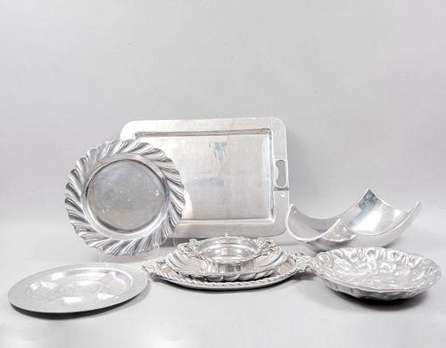 Lote de 8 piezas. Siglo XX. Elaboradas en pewter y aluminio. Consta de: plato botanero, platón, 2 charolas y 4 centros de mesa.