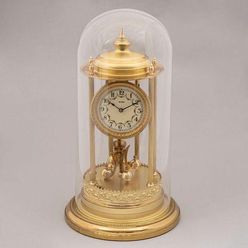 Reloj de mesa. Alemania. Siglo XX. Diseño arquitectónico. En latón dorado. Mecanismo de péndulo. Con capelo de vidrio. 43 x 23 cm Ø