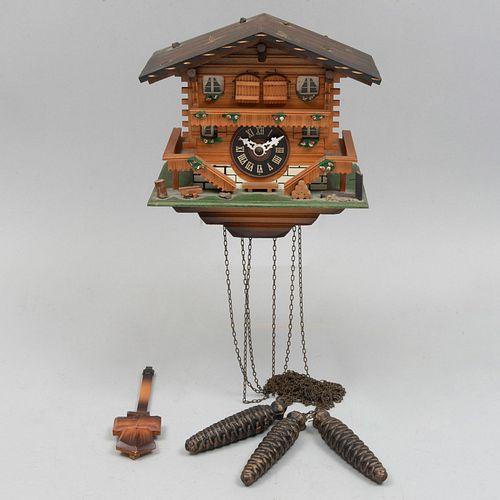 Reloj cucú. Alemania. Siglo XX. Diseño a manera de cabaña. En talla de madera policromada. Mecanismo de péndulo y contrapesos.