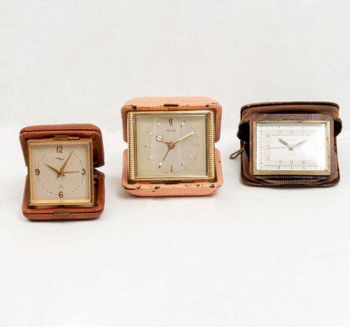 Lote de 3 relojes de viaje. Alemania y Suiza, s XX. Elaborados en metal dorado. Consta de: Marca Kienzle, Mecanismo de cuerda. Otros.