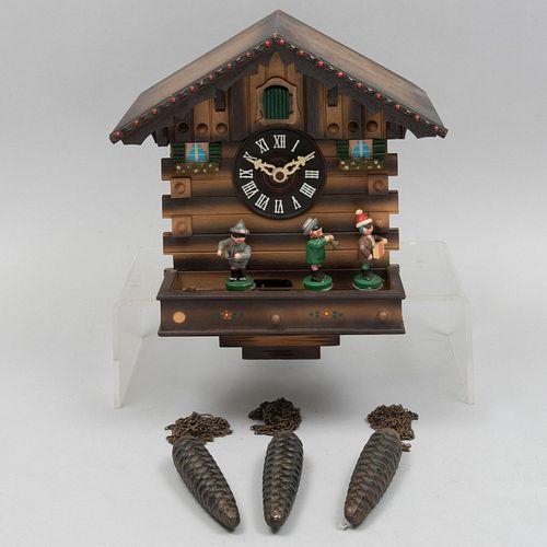 Reloj cucú. Siglo XX. Diseño a manera de cabaña. En talla de madera policromada con aplicaciones sintéticas. Mecanismo con contrapesos.