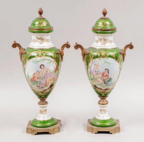 Par de tibores. Francia, siglo XX. Elaborados en porcelana limoges, color verde. Con aplicaciones de metal dorado en bases.