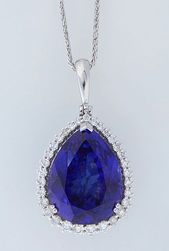 Platinum Pendant, with a 40.84 carat pear shaped tanzanite, atop a conforming border of round diamonds, on a platinum snake chain, total diamond wt.-