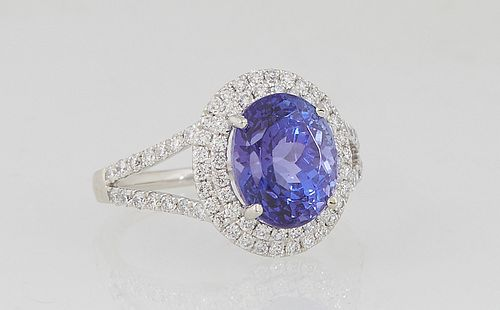 Lady's Platinum Dinner Ring, with an oval 4.05 tanzanite atop a conforming double graduated border of round diamonds, the split shoulders of the band