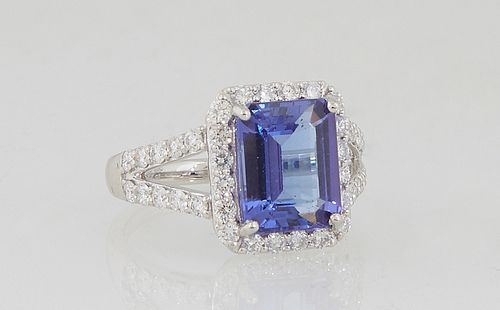 Lady's Platinum Dinner Ring, with an emerald cut 3.64 carat tanzanite atop an octagonal border of small round diamonds, the split shoulders of the ban