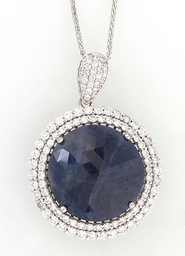 Platinum Pendant, with a 42.65 carat round blue sapphire atop a double concentric graduated border of round diamonds, with a diamond mounted bail, on