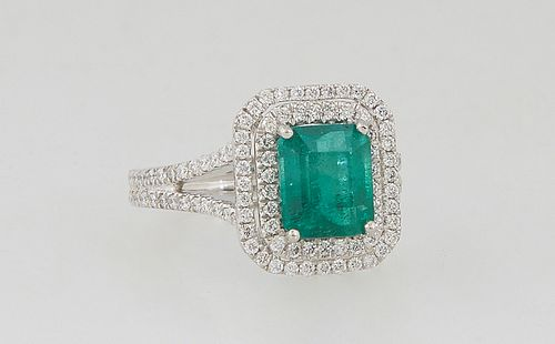 Ladys's Platinum Dinner Ring, with a 2.35 carat emerald atop a double graduated octagonal band of small round diamonds, the split shoulders of the ban