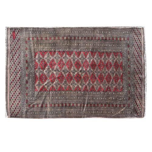 Tapete. Siglo XX. Estilo bokhara. Elaborado a mano, en fibras de lana y algodón. Decorado con motivos geométricos.