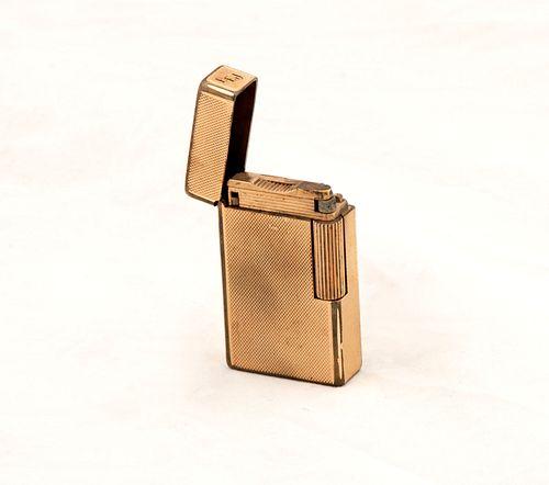 Encendedor Dupont. Cuerpo rectangular en acero dorado con grabados en forma de rombos y monograma AEJ.