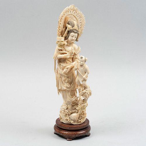 Quan Yin con Dharma y niño. China, siglo XX. Talla en marfil con detalles en tinta negra y base de madera. 31 cm de altura