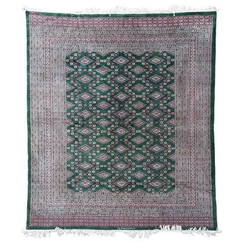 TAPETE SIGLO XX IRAN ESTILO TEKKE Elaborado en lana Decorado con motivos geométricos sobre fondo verde Firmado 280 x 250 cm.