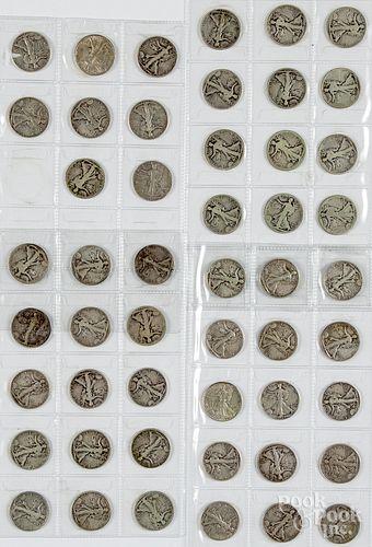 Fifty-one Walking Liberty silver half dollars.