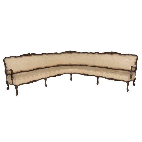 Sala esquinera. SXX.  Talla en madera. Con respaldo cerrado y asiento en tapicería color beige.