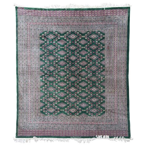 Tapete. Irán. SXX. Estilo Tekke. Elaborado en fibras de lana. Decorado con motivos geométricos sobre fondo verde. Firmado. 280 x 250 cm