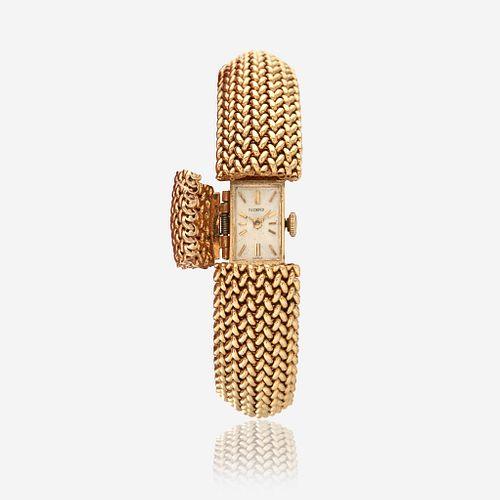 A fourteen karat gold, covered dial bracelet wristwatch