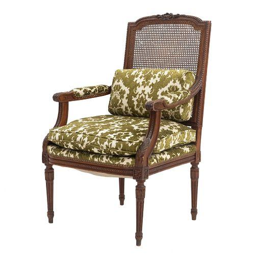Sillón. Siglo XX. Talla en madera. Con respaldo de bejuco y asiento con cojines en tapicería color verde.