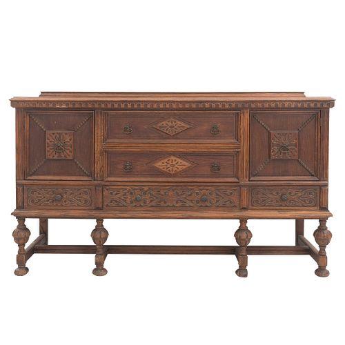 Trinchador. Siglo XX. Elaborado en madera. Con cubierta rectangular, 2 puertas, 5 cajones, chambrana compuesta y soportes tipo bollo.
