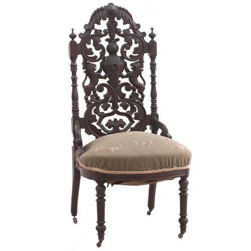 Silla. Siglo XX. Elaborada en madera. Diseño calado. Con asiento de tela color verde, fustes anillados y soportes tipo carrete.