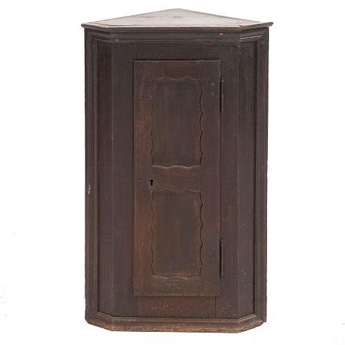 Esquinero. Siglo XX. Elaborado en madera. Con puerta abatible y 3 entrepaños internos. Decorado con molduras.