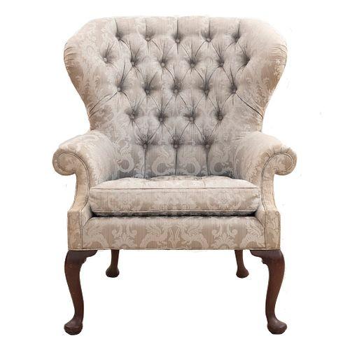 Sillón. SXX. Talla en madera. Marca Baker. Con respaldo cerrado capitonado y asiento con cojín en tapicería color beige.