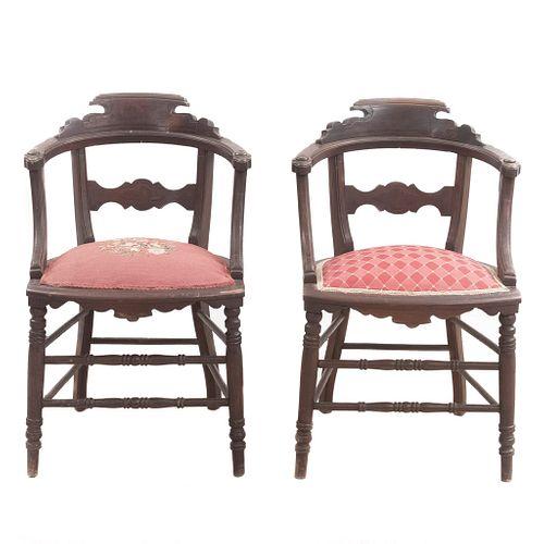 Par de sillones. Siglo XX. Elaborado en madera tallada. Con respaldos semiabiertos, asientos de tela, chambrana de caja, fuste anillado