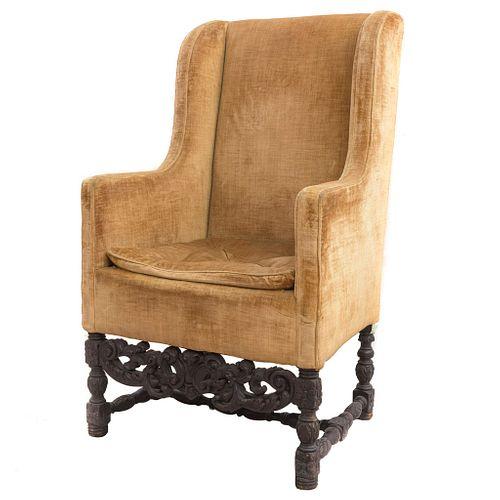Sillón. SXX. Talla en madera. Con respaldo cerrado y asiento con cojín en tapicería aterciopelada color ocre.