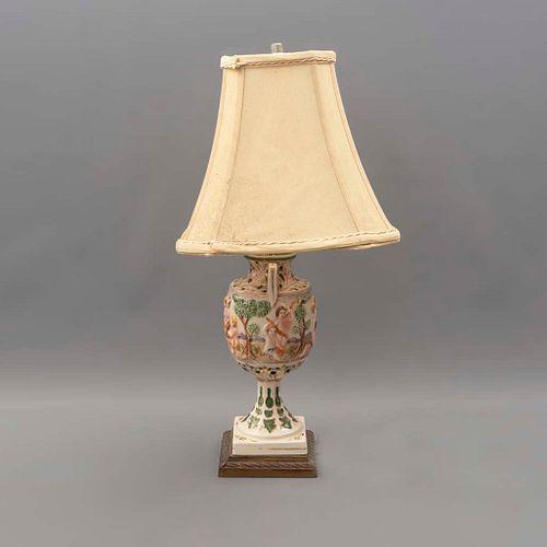 Lámpara de mesa. SXX. Elaborada en porcelana tipo Capodimonte. Para una luz. Con pantalla de tela y fuste a manera de jarrón.