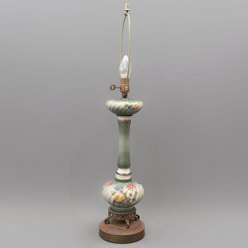 Lámpara de mesa. Siglo XX. Elaborada en cerámica. Para una luz. Con base circular de metal. Decorada con motivos florales.