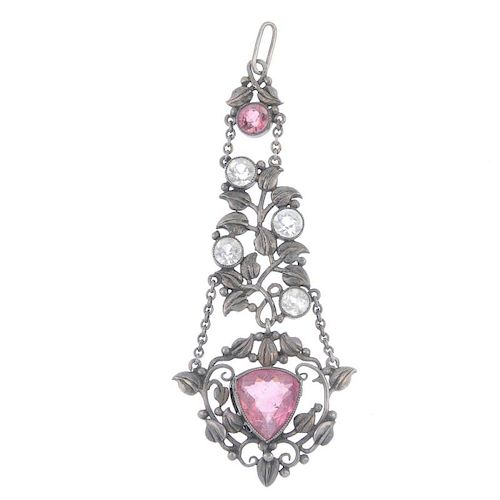An early 20th century silver tourmaline and topaz pendant. The central triangular pink tourmaline wi