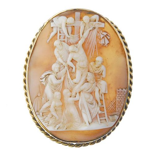 A cameo brooch. Of oval outline, the shell cameo carved to depict Christ's crucifixion, to the rope-