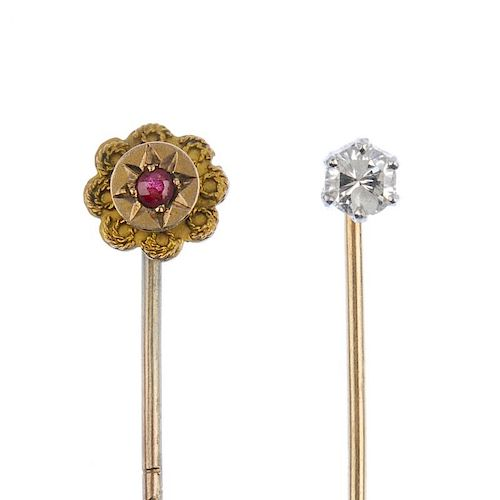 Two stickpins. The first designed a single brilliant-cut diamond stickpin, the second of floral outl