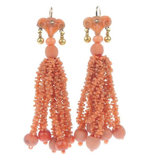A pair of coral ear pendants. each designed as a carved ram mask, suspending a series of carved cora