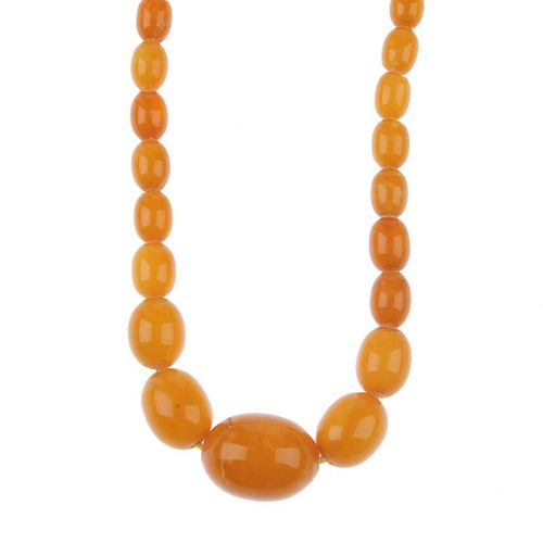 A natural amber necklace. Designed as thirty-five graduated oval-shape beads measuring 8 to 2.2cms,