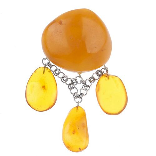 A natural amber brooch. The irregular-shape translucent polished amber panel, suspending three oval-