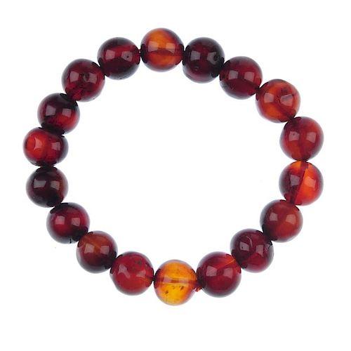 A natural Burmese blood amber bracelet. Comprising eighteen spherical beads measuring 11mm, strung t