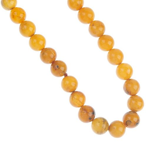A natural amber necklace. Comprising thirty-nine spherical beads, measuring 1.8cms. Length 66cms. We