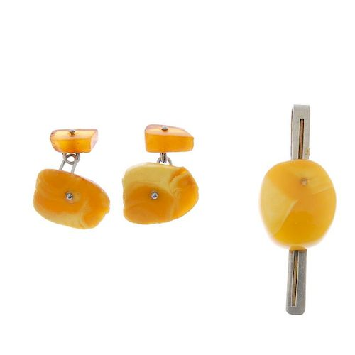 A natural amber tie slide and a pair of cufflinks. The natural amber to the tie slide, of oval outli