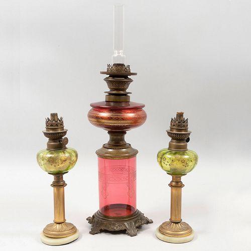 Lote de quinqué y par de lámparas de mesa. Finales del SXIX. Elaboradas en metal dorado y vidrio. Marcas Kosmos y Stobwasser.