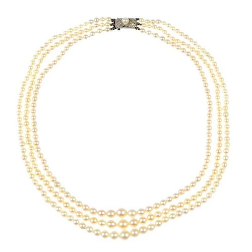 A cultured pearl necklace and an imitation pearl brooch. The cultured pearl necklace of three gradua