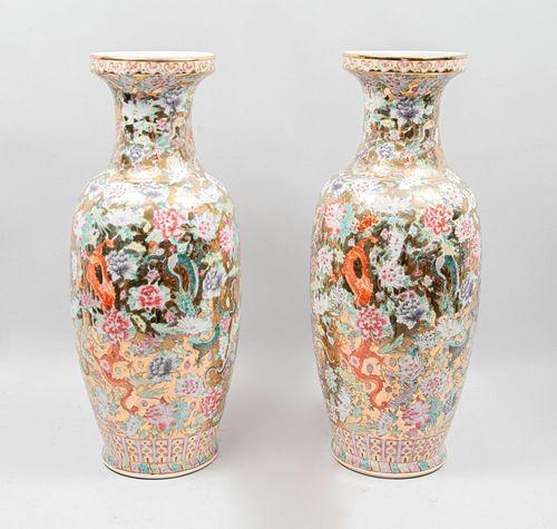 Par de jarrones. Origen oriental, SXX.  Elaborados en porcelana.  Decorado con motivos orientales , vegetales y esmalte dorado. 82 cm