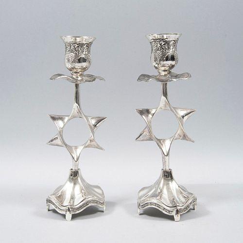 Par de candeleros. SXX. Elaborados en plata baja ley y metal plateado. Fuste a manera de estrella de David. Peso aprox. 460 g