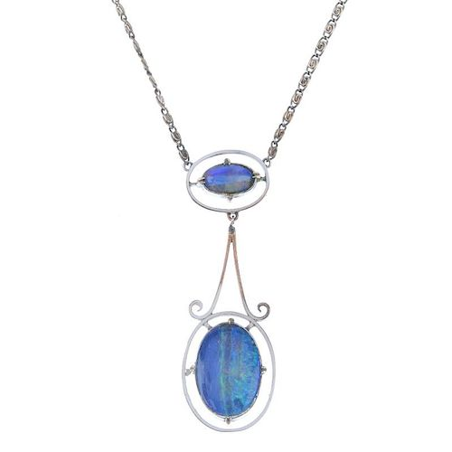 An opal pendant. Designed as an oval opal cabochon, within a halo surround, to the scrolling link, s