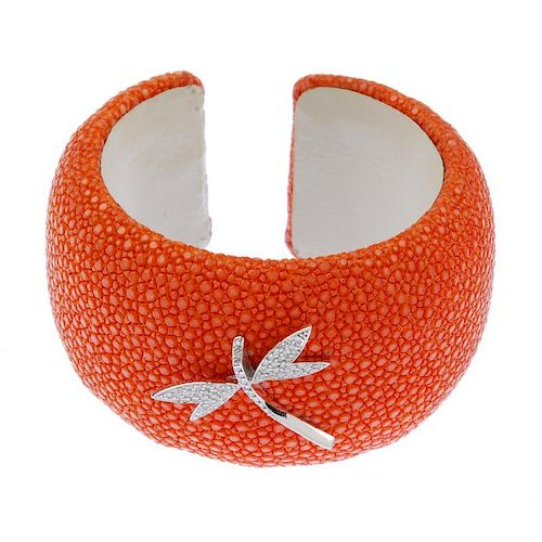 A diamond and stingray dragonfly cuff. The brilliant-cut diamond dragonfly, atop a dyed orange sting