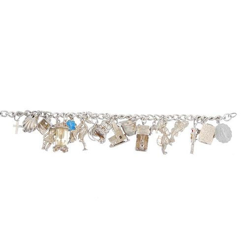 A charm bracelet. Designed as a series of nineteen charms, to include a shell and a steam train, sus