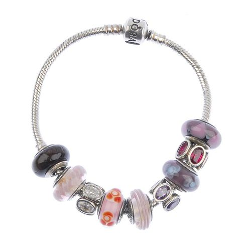 PANDORA - a charm bracelet. With nine charms including five glass charms, one wooden charm and three
