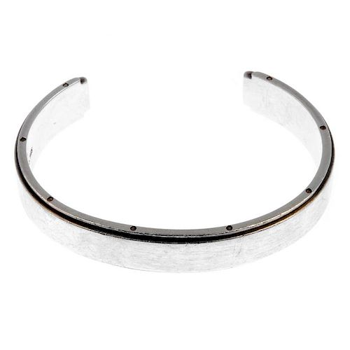 TIFFANY & CO. - a bangle. The open bangle with screw detail to the edges and plain front. Signed Tif